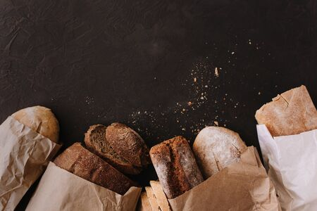Various crispy bread and buns on the stone table, Loaf of fresh baked artisan sliced rye bread over dark texture background. 스톡 콘텐츠
