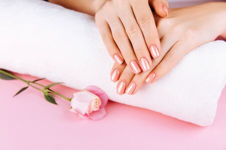 Beautiful Woman Hands with fresh eustoma. Spa and Manicure concept. Female hands with pink manicure. Soft skin, skincare concept. Beauty nails. Over beige background 스톡 콘텐츠 - 140046063