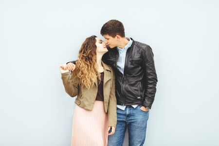 Happy loving couple isolated on gray background. stylish image, good mood, kiss in love