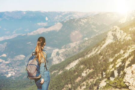 Young beautiful girl travels alone in the mountains in spring or autumn, looks into the distance and enjoys nature, rocks and green forests, view of the landscape. a backpack behind and sportswear, freedom and lightness