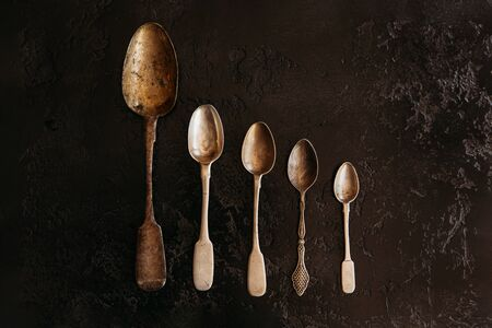 Three empty old silver spoons on dark background. vintage on stone table. Top view