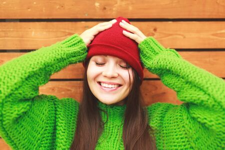 Attractive laughing female standing against wooden wall background with copy space area, pretty casually-dressed hipster woman looking away smiling and feeling so happy in joy