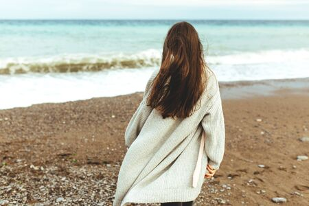 A beautiful young girl walks along the seashore, a storm, hair fly apart, a gray cardigan, a sports figure, in sneakers, enjoys, autumn or winter