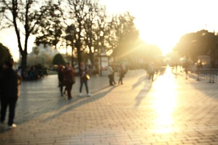 People in bokeh, blurred street view, sunset Imagens