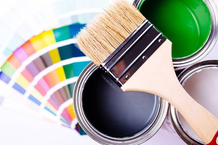 Paint brush laying on a heap of color samples. open can of green paint