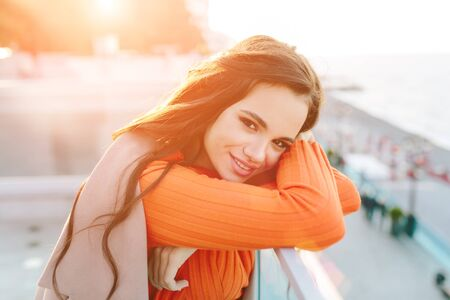Close up shot of good looking female tourist enjoys free time outdoor near ocean or sea, looks at camera during leisure on sunny autumn day, poses for selfie. Happy smiling girl.