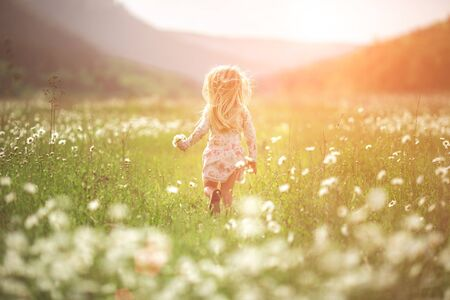 Little beautiful girl runs on the street or in the park laughing, across the field. sunset light, childhood. Emotional portrait of a happy and kind girl with wavy hair looking with a smile while sitting in a field of daisies in the sunset rays during summer vacation. 스톡 콘텐츠