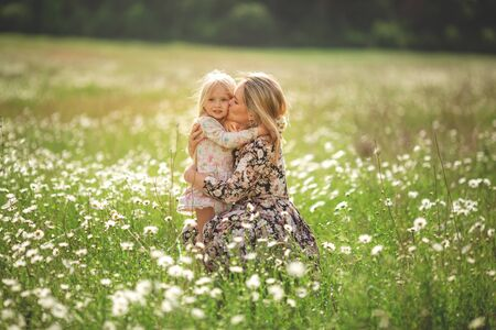 Beautiful young mother with her daughter on a field with daisies sunset sun, life style, concept of motherhood, walk in the park or in nature.