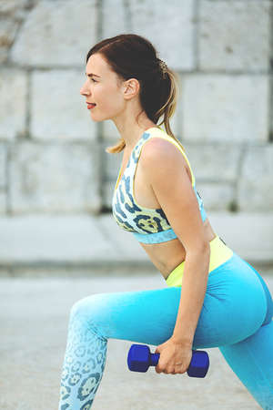Young beautiful woman squats with dumbbells outside