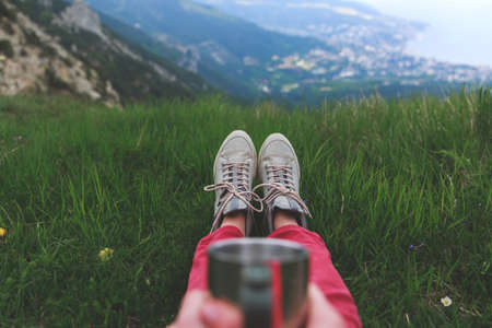 Closeup photo of cup with tea in travelers hand over out of focus mountains view. A young tourist woman drinks a hot drink from a cup and enjoys the scenery in the mountains. Trekking concept