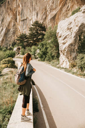 Traveling woman sitting near mountain and looking far away Spring weather, calm scene. Hiking outdoors, landscape view in the sunlight. A series of photos of Wanderlust. 스톡 콘텐츠