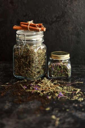 Jars of different leaf teas on dark background