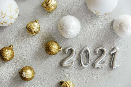 Happy New Year 2021. Silver digits 2021 with christmas hat are on white background. Holiday Party Decoration or postcard concept with top view and copy space.