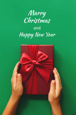 Childs hands holding Red gift boxes on green background. Christmas card. Flat lay. Top view with space for text 스톡 콘텐츠