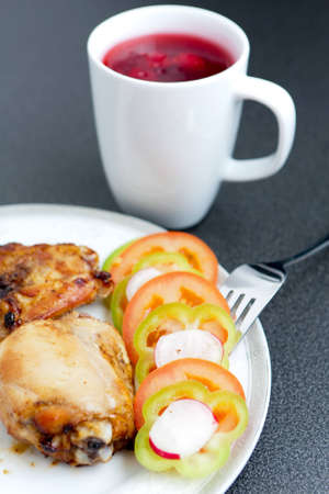 Crisp golden fried chicken pieces on a plate with sliced peppers and tomato, served with fresh red fruit juice. photo