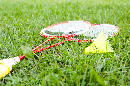 long handled: Two badminton rackets and a shuttlecock lying on green grass in summer sunshine. Stock Photo