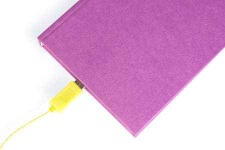 A violet-coloured closed book with a yellow cable connector leading in to the pages, isolated on white photo