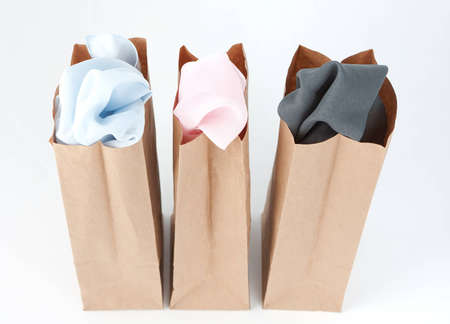 Varied colors of cloth in each of three brown paper bags photo