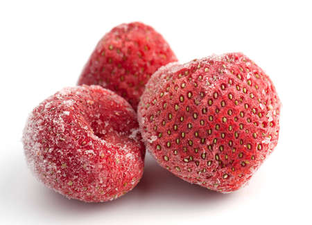 Three frozen strawberries covered in frosted ice on a white background. Stock Photo