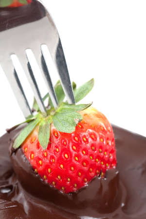A juicy ripe red strawberry on a fork is dipped into a bowl of delicious melted brown chocolate