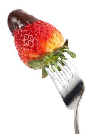 A ripe red strawberry with its end dipped in brown chocolate is held ready to eat on a fork