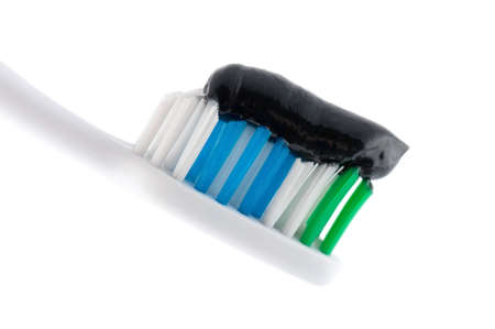 A toothbrush with black toothpaste over white in a dental hygiene and tooth care concept Stock Photo