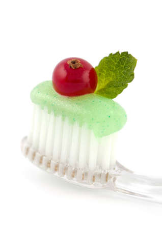 Fresh minty toothpaste on a clear toothbrush with a green mint leaf and red cranberry on white photo