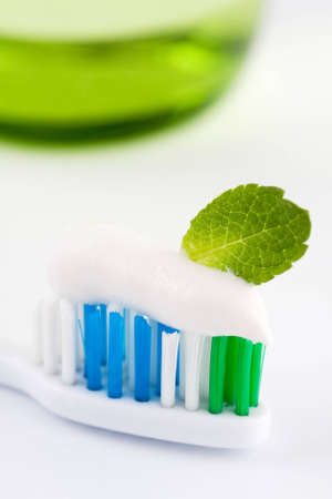 Closeup of the head of a toothbrush with fresh white toothpaste and a green mint leaf, conceptual of oral freshness