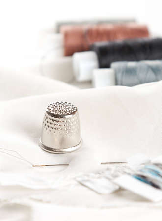 Sewing accessories on white surface. Thread, needle and thimble - selective focus Stock Photo - 13389917