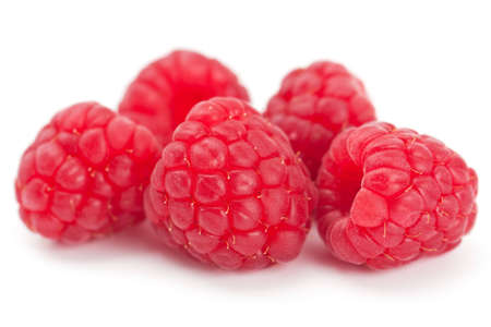 Studio closeup on white of five luscious ripe red juicy fresh raspberries with shallow depth of field Stock Photo