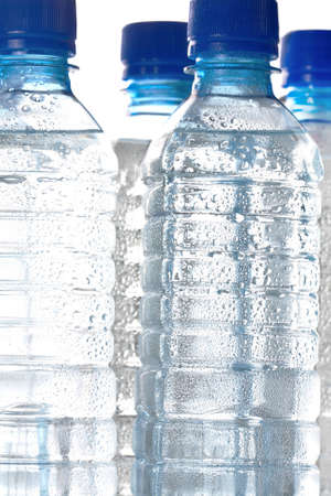 unlabelled: Clear unlabelled plastic bottles of healthy pure cold bottled water with water droplets on the exterior of the bottle