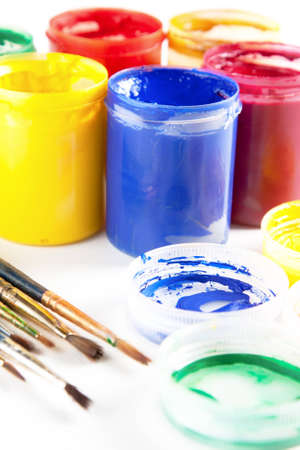 Opened colourful tubs of paint and paintbrushes displayed on a white background in an arts and crafts concept Stock Photo