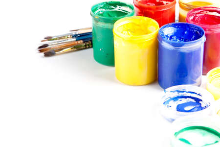 Jars of brightly coloured gouache paint with artists brushes and copyspace on a white background