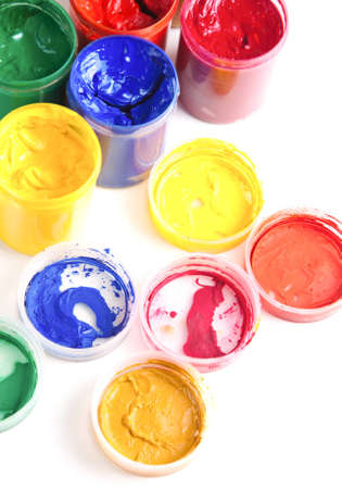 Overhead view of colourful bright pots of gouache paint with their lids off on a white background