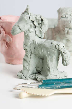 Modelling a horse from clay or plasticine in a creative craft class with sculpting tools in the foreground Stock Photo - 13646245