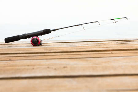 Unattended fishing rod, line and reel lying on a wooden deck reading to enjoy a day of sport fishing Stock Photo - 13646236