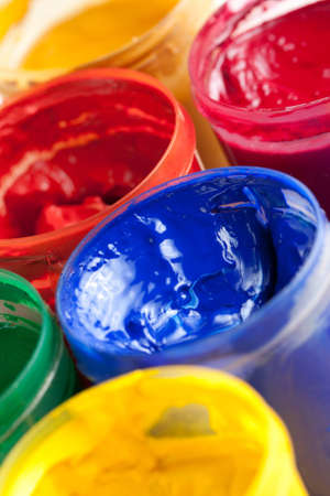 Overhead view of colourful bright pots of gouache paint with their lids off on a white background Stock Photo - 13646247