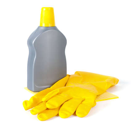 A pair of yellow rubber gloves lies in front of an unlabelled grey detergent bottle in a cleaning and hygiene concept Stock Photo
