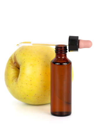 Brown bottle with dropper in front of apple isolated against white background Stock Photo