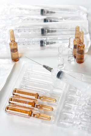 Syringes and ampoules on white surface - medical concept Stock Photo