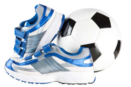 A pair of sports trainers or shoes together with a black and white soccer ball or football in a sports concept