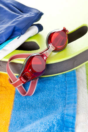 Colourful beach towel with a pair of protective red swimming goggles resting on the edge of a board in a leisure and sport concept Stock Photo