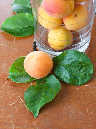 Fresh apricot lying on three leaves on a scratched grungy brown rustic tabletop alongside a jar containing additional fruit Stock Photo - 14442545