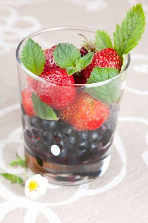 glass topped: Whole fresh juicy ripe blackberries and strawberries in a transparent glass topped with green mint leaves