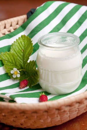 Glass pot of creamy natural yoghurt on a colourful striped green and white napkin in a basket Stock Photo