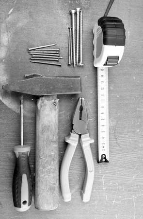 Black and white image of assorted DIY tools on a workbench top for home maintenance and repair Stock Photo