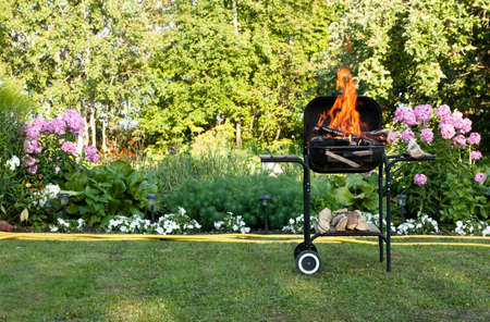 Flames burning in a barbecue standing in a pretty garden as the coals are prepared for grilling an array of meat for a lunchtime cookout Stock Photo