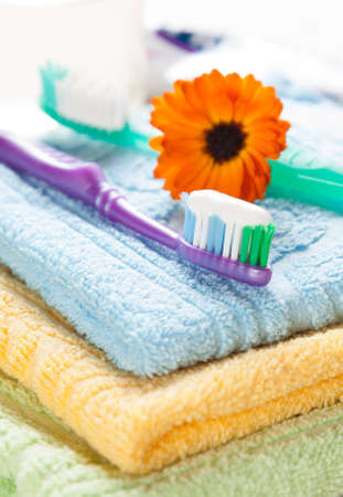 Toothbrushes with toothpaste resting on a pile of fresh towels with a calendula flower