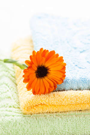 bathtowel: Colorful towels and orange flower on top of them - spa concept