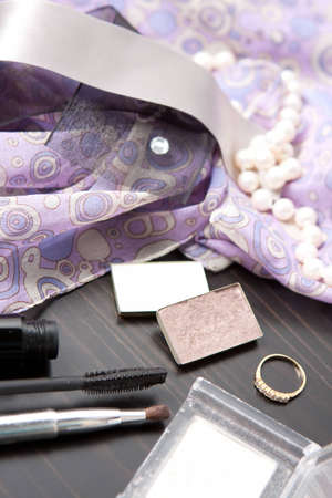 Cosmetics and jewellery on a tabletop with a ring and string of pearls on pretty patterned lilac fabric